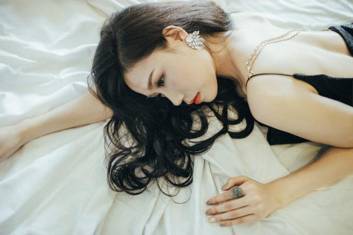 ドレス姿でうつ伏せに寝転んでいる女性