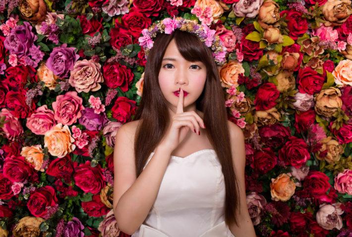 花かんむりをして口元に人差し指をあてている女性