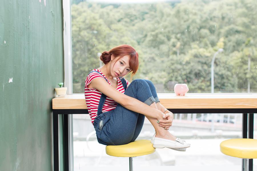 椅子の上で三角座りしている女性