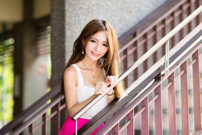 階段の手すりに手をおいている女性
