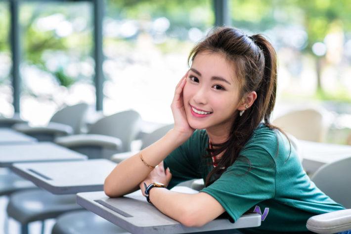 教室の机で頬杖をついている女性