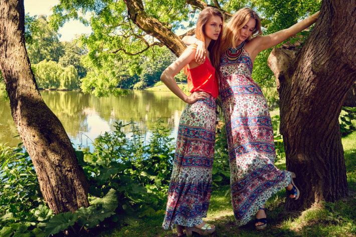 湖の前でポーズを取ってはしゃいでいる女性2人