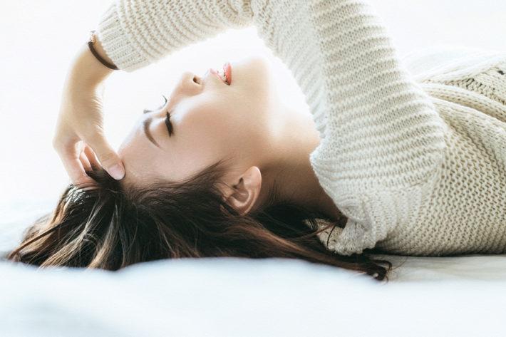 仰向けに寝転んで考え事をしている女性
