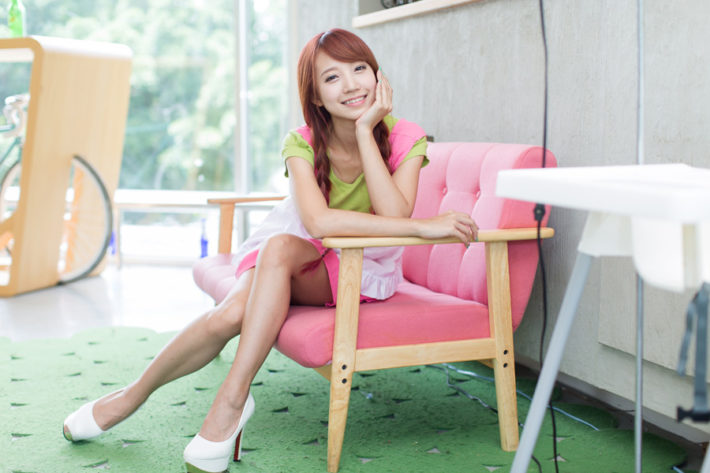 ソファーに座って微笑んでいる女性
