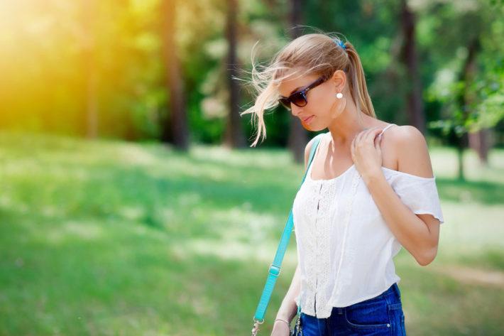 サングラスをして公園を歩く女性