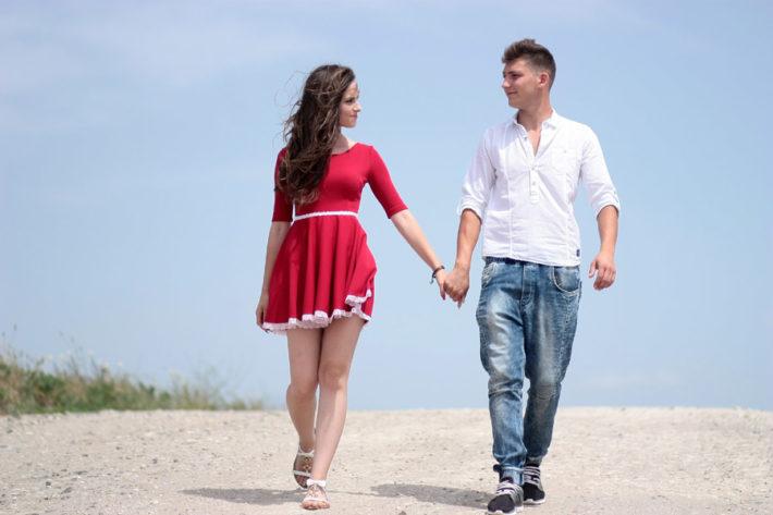 手をつないで浜辺を歩く外国人の男女