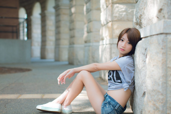 Tシャツと短パンを着て地面に座っている女性