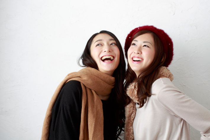 笑いながら天井を見上げている女性2人組