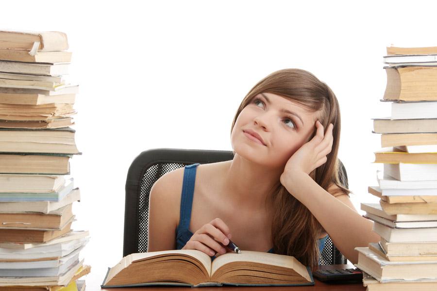 山積みの本に囲まれて考え事をしている女性