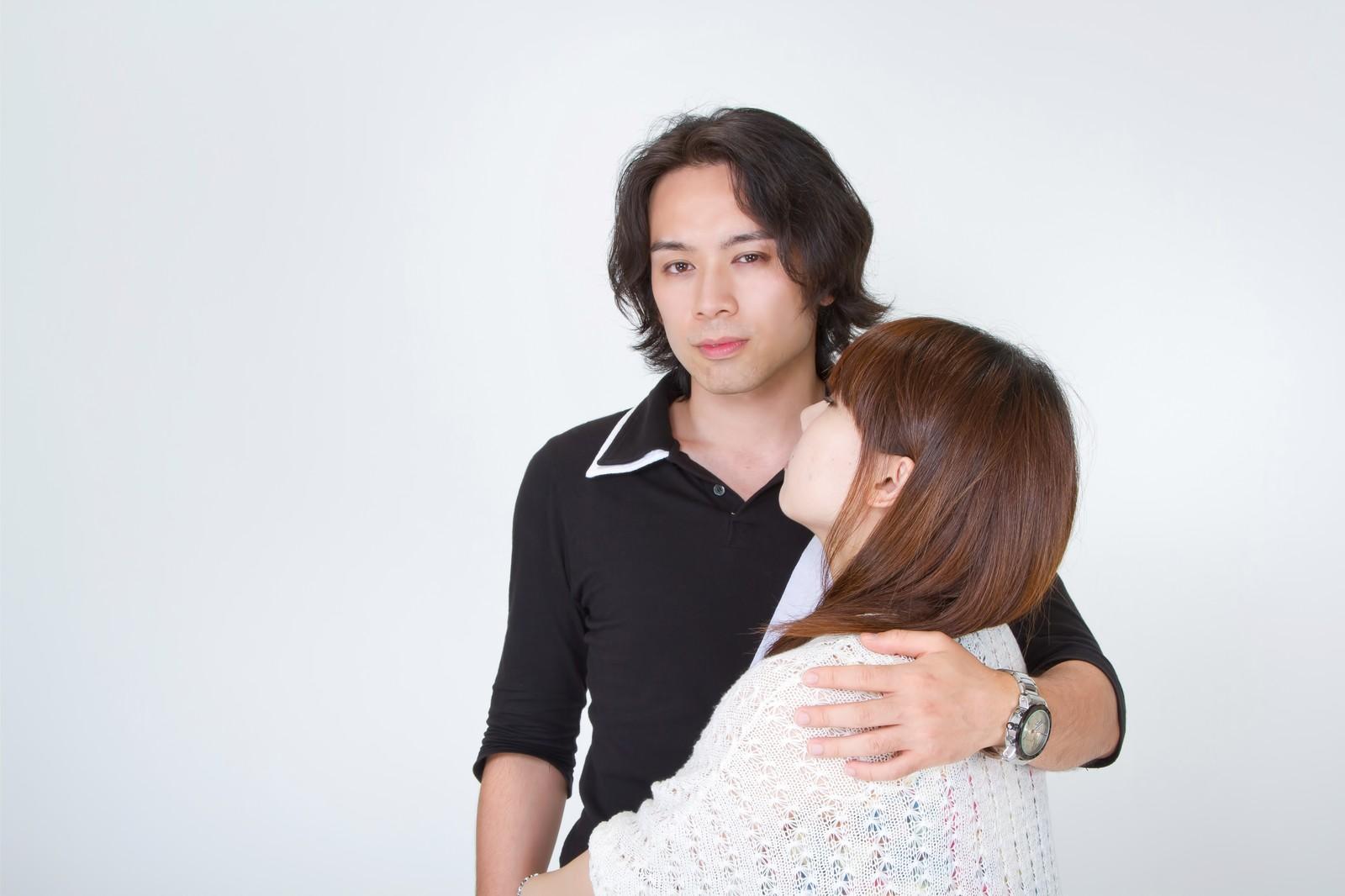 女性の肩に手を回し悪巧みしている顔の男性