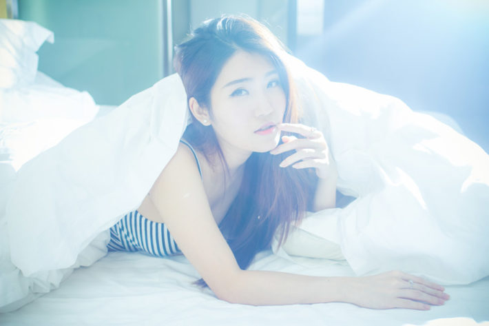 ベッドでシーツを羽織りうつ伏せになっている女性