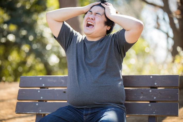 公園のベンチで頭を抱えて悩んでいる男性