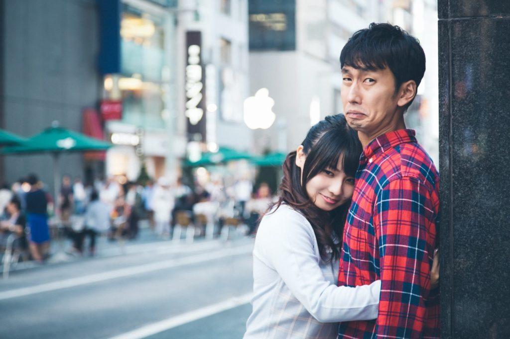 可愛い子から抱きしめられているのにしかめっ面の男性