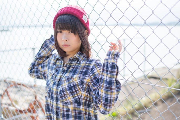 フェンスに持たれているネルシャツを着た女性