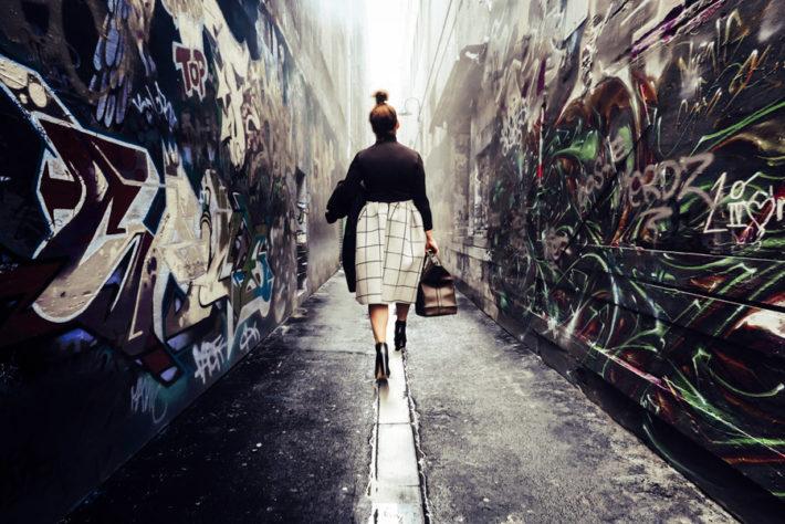 路地裏を歩き去っていく女性の後ろ姿