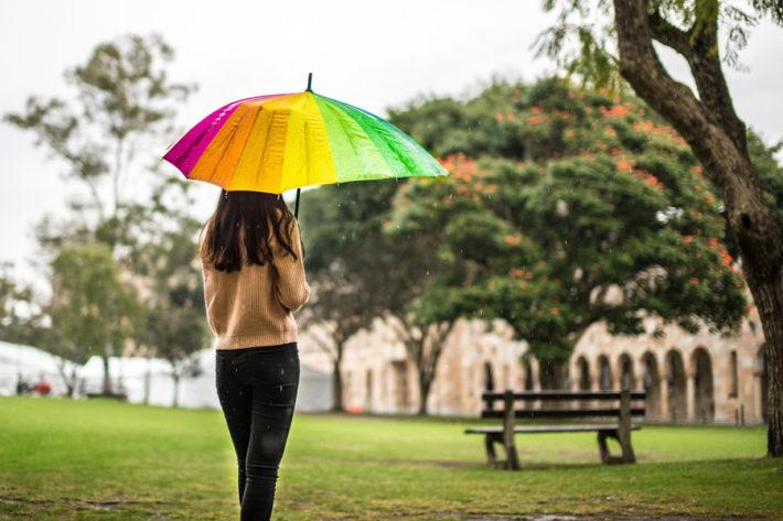 公園で傘をさしている女性の後ろ姿