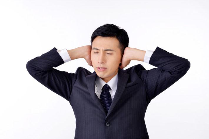 耳をふさいでいる男性