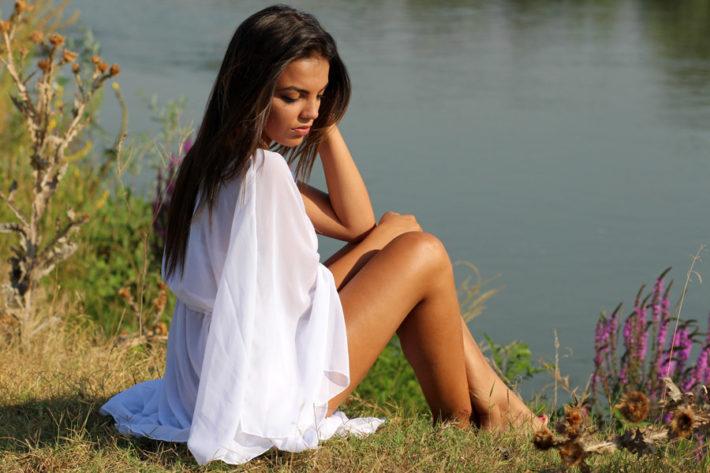 湖のほとりで座っている女性