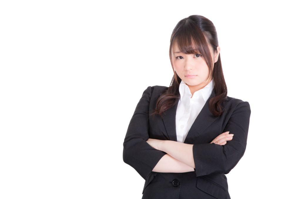 腕を組んでいるスーツ姿の女性