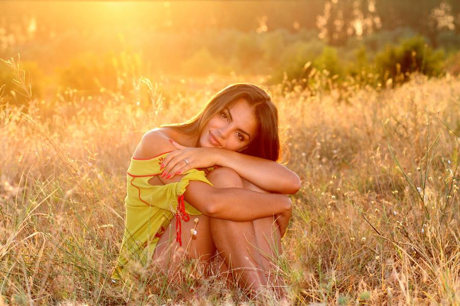 草原で膝を抱えている女性