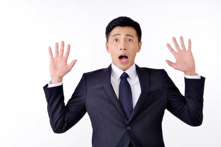 手を広げて驚くスーツ姿の男性