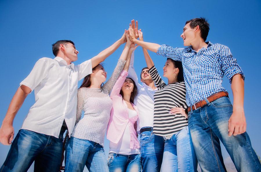 青空に手を掲げて掌を合わせている男女