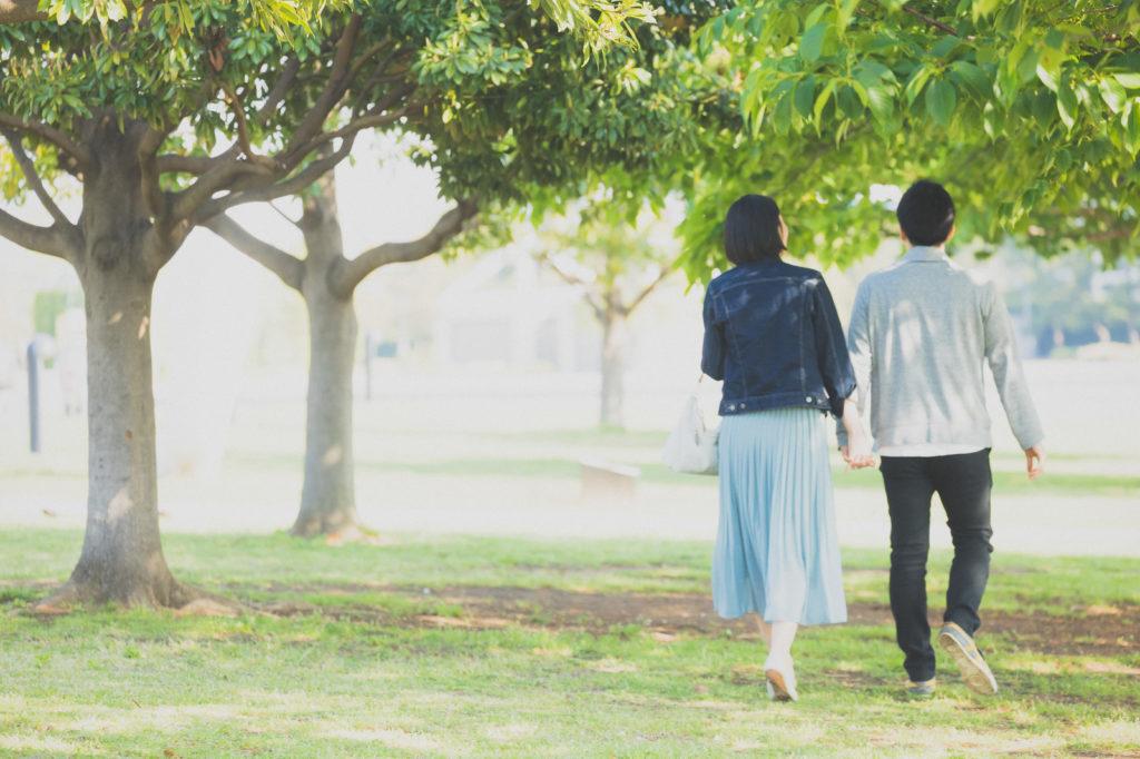 寄り添い合って公園を歩いている男女の後ろ姿