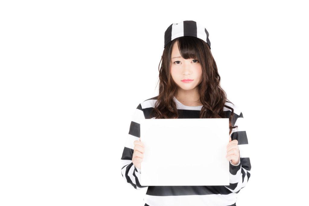 囚人服のコスプレをした女性が真っ白な保ワイドボードを出している画像