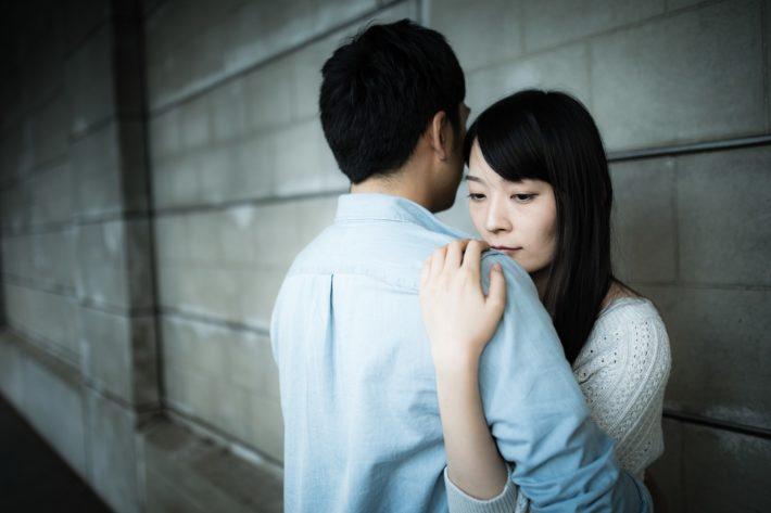 悲しそうな顔で抱きしめられている女性