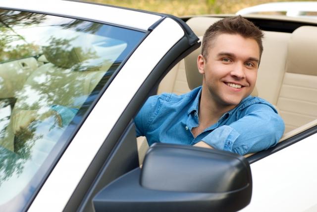 運転席に座っている笑顔のイケメン外国人男性