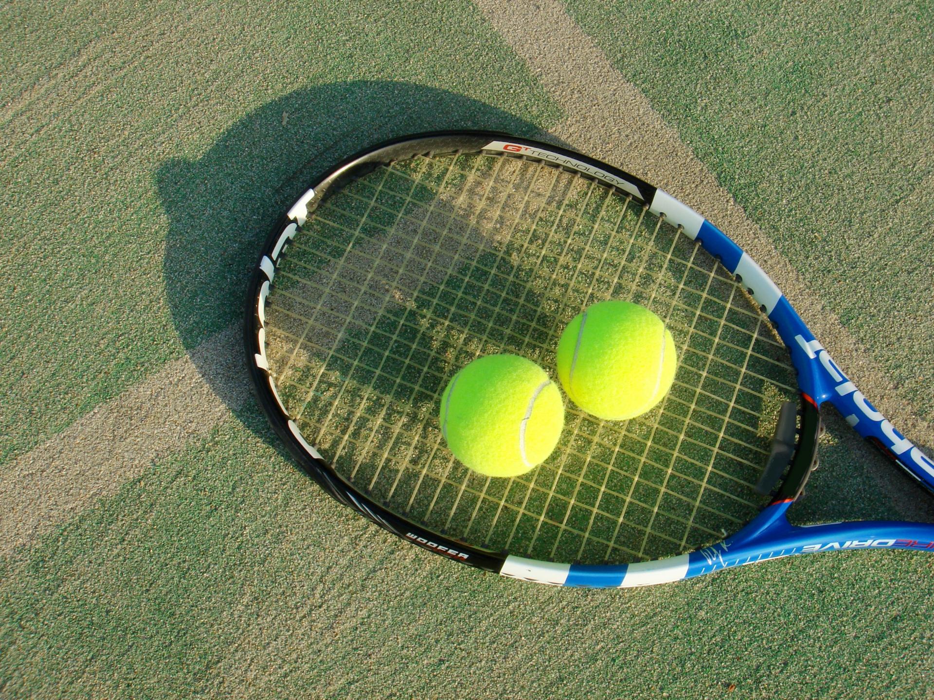 コートの上に置かれたテニスラケットとボール
