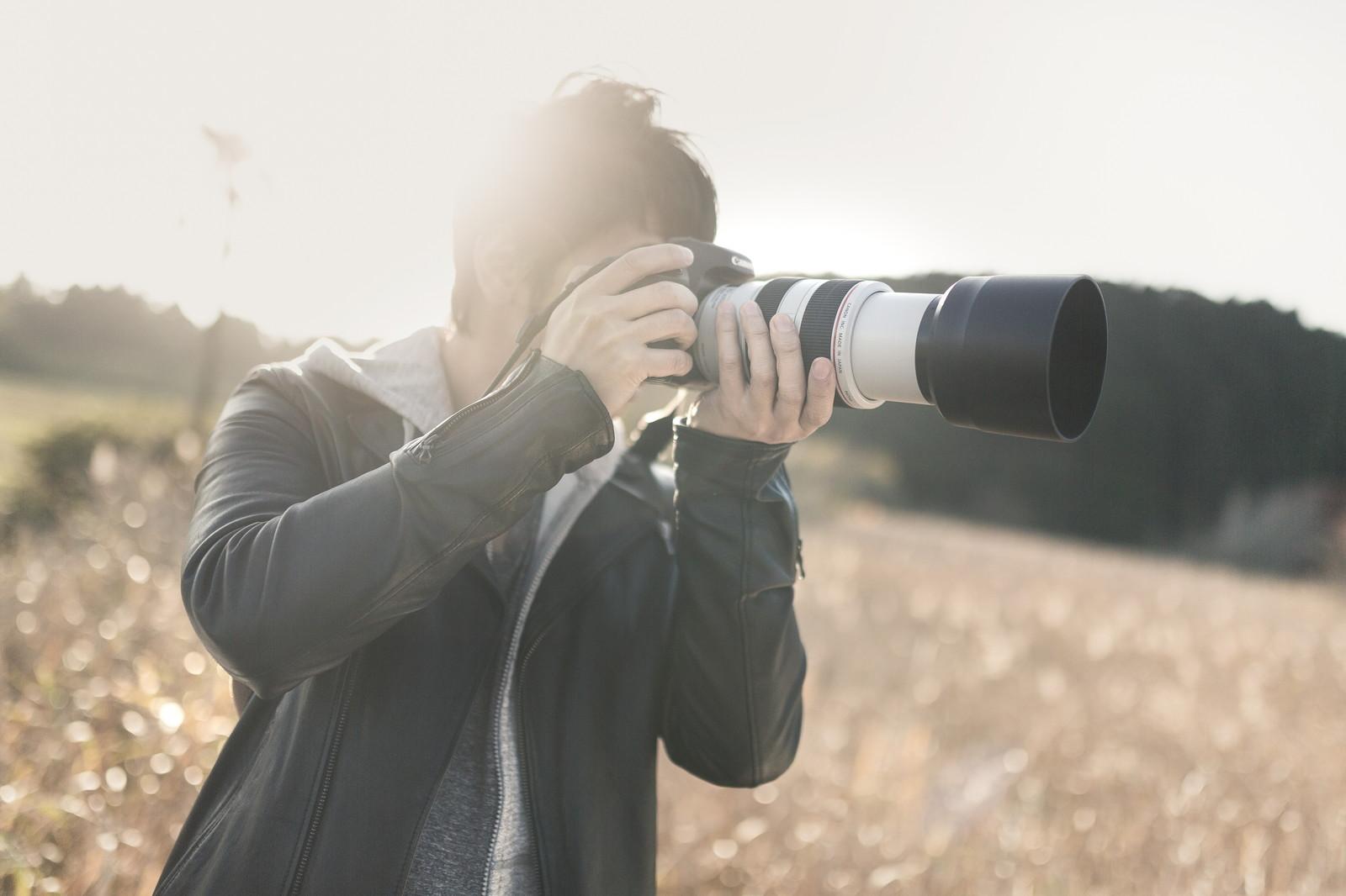 望遠カメラで風景を撮影している男性