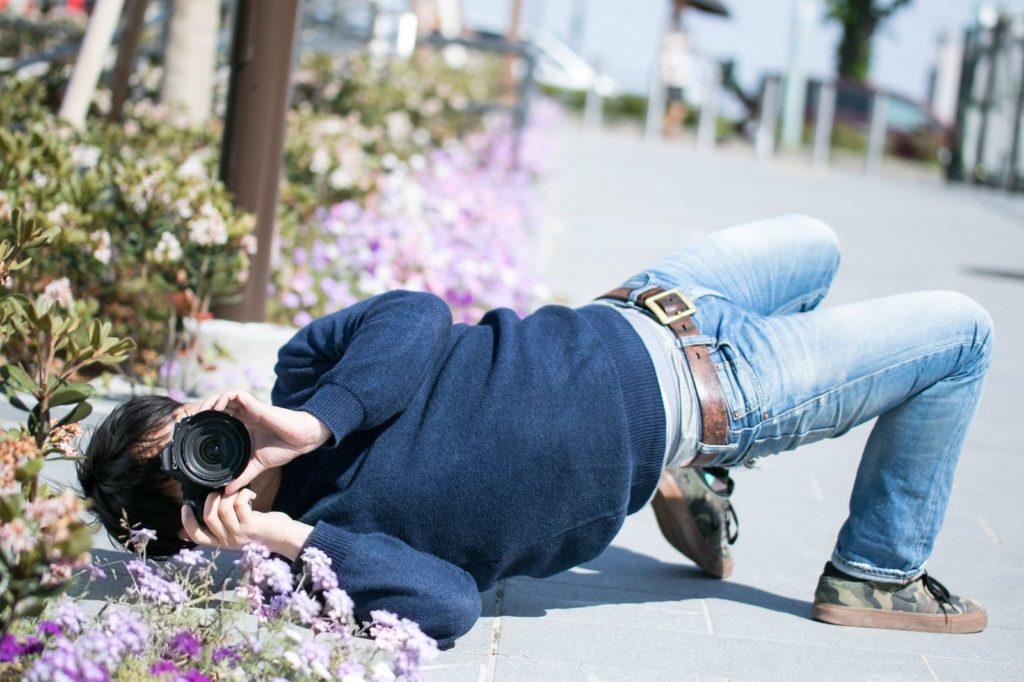 道端に寝そべって写真を撮っている男性