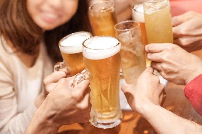 飲み会でわいわい乾杯している男女