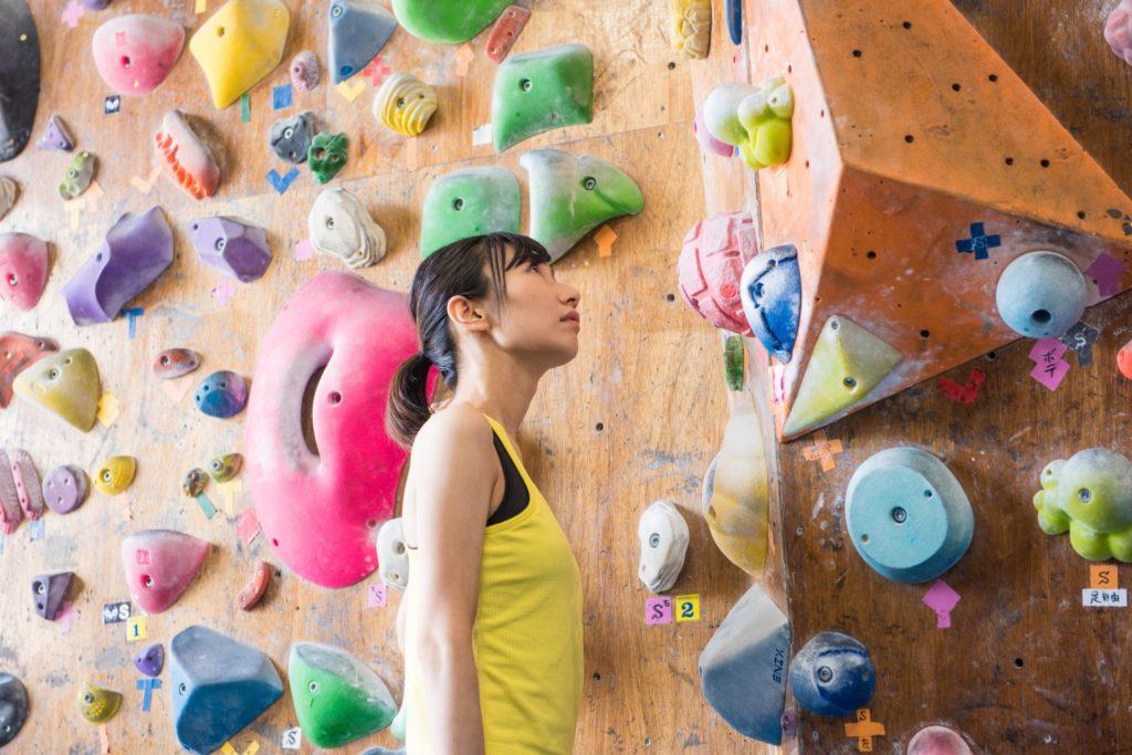 ボルダリングで壁を見つめている女性