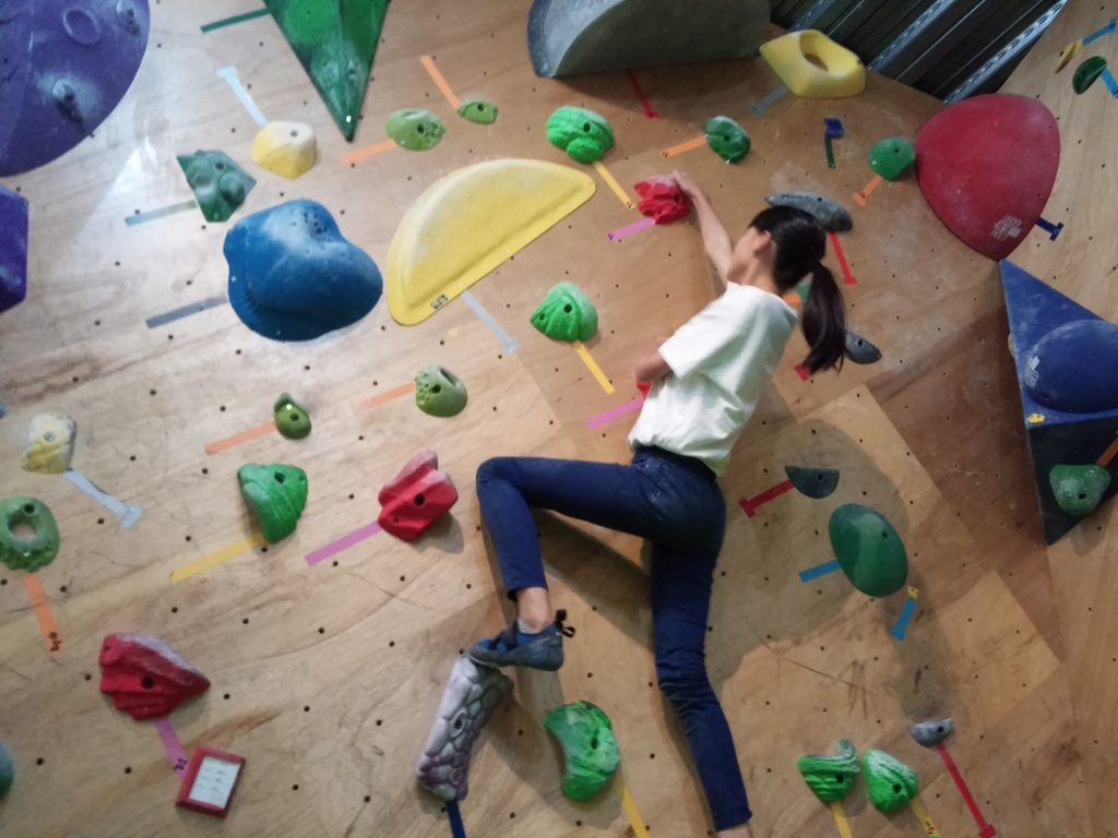 ボルダリングで壁を登っている女性