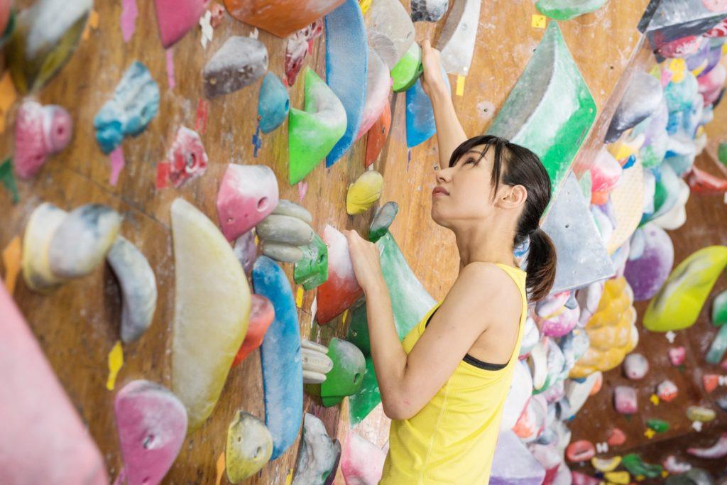 ボルダリングのホールドを登っている女性