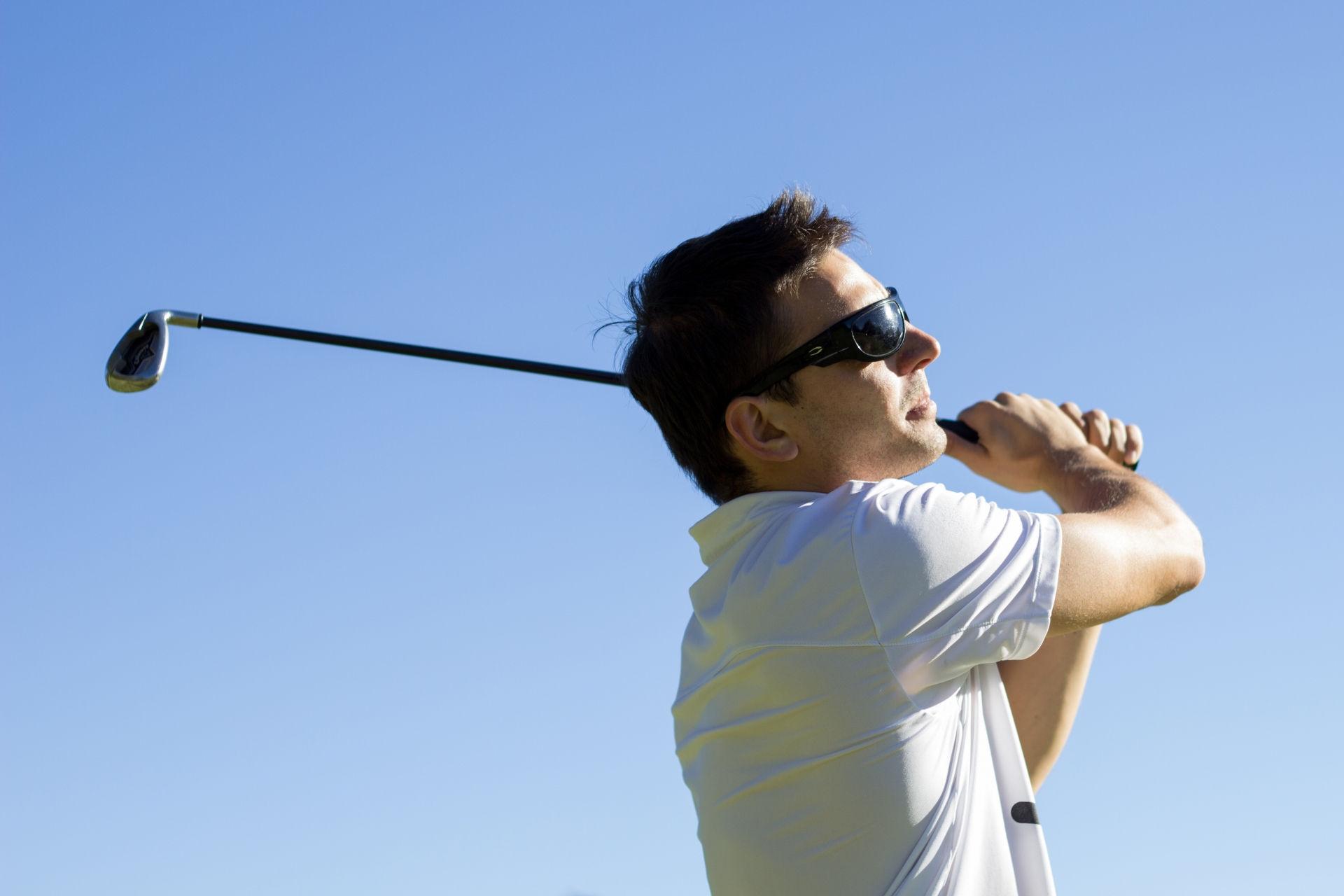 ゴルフでショットしている外国人男性