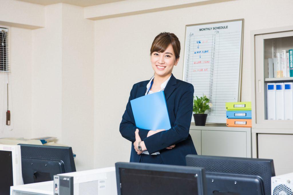 スーツ姿でオフィスに立っている女性