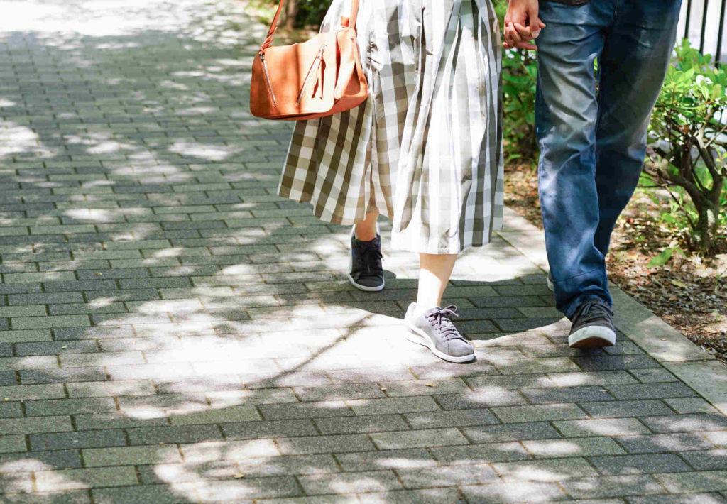 手をつないで街を歩いている男女