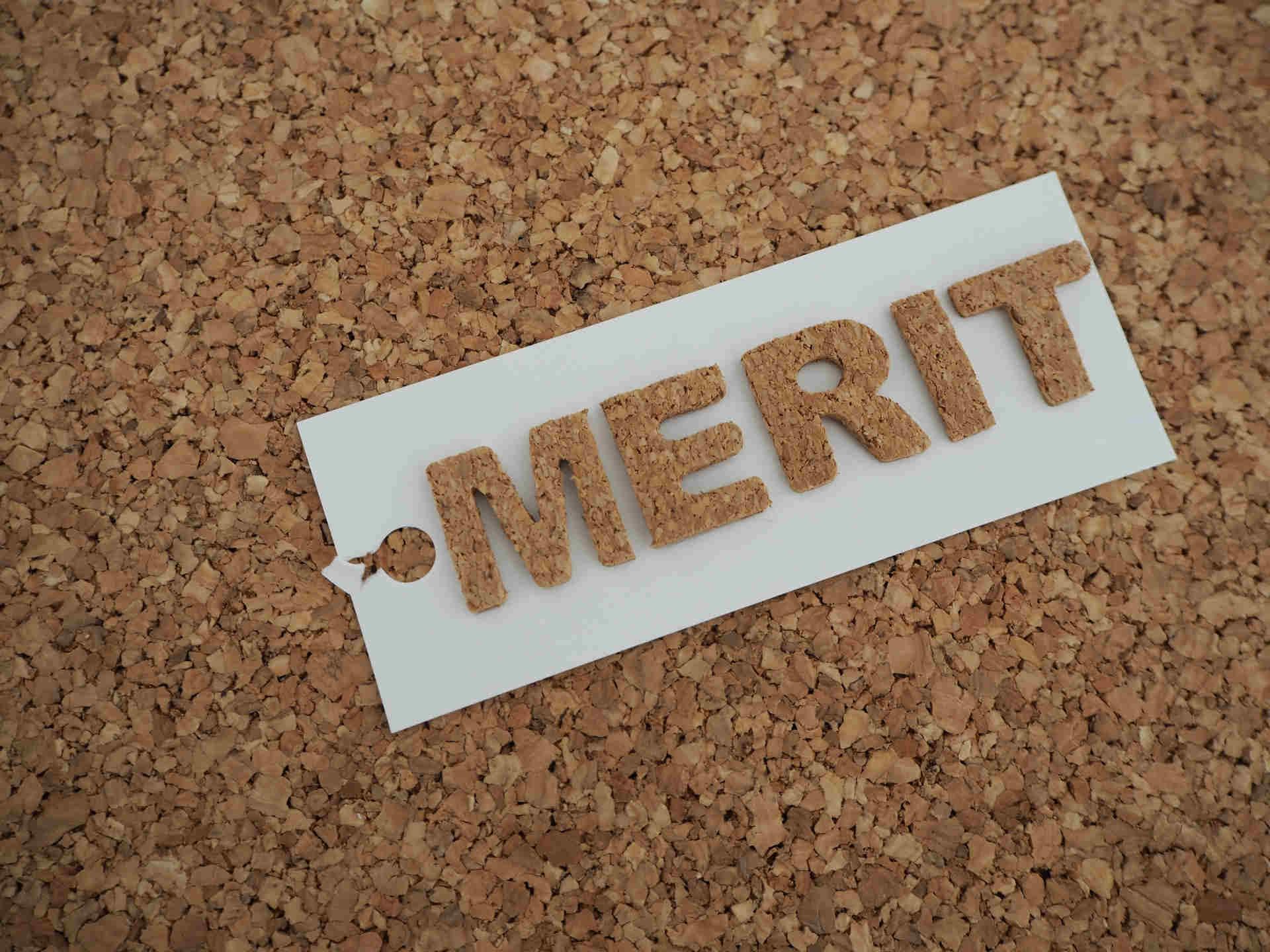 コルクボードに書かれたメリットの文字