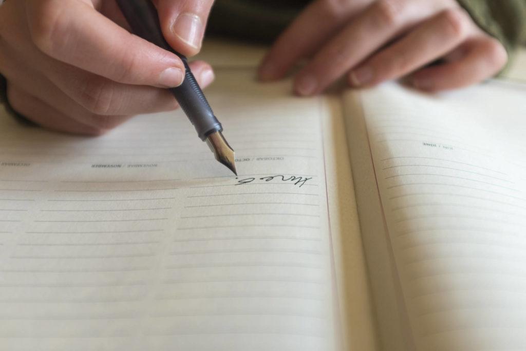 文字を書く男性の手元
