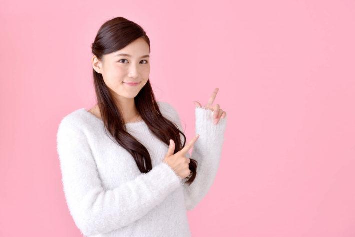 両方の指を指している女性