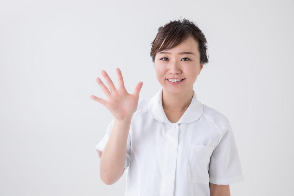 白衣の女性が手を広げ、5を示している画像