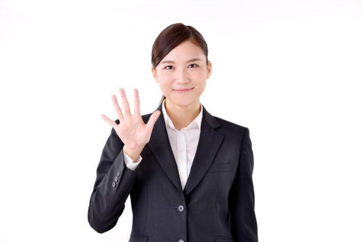 スーツの女性が手を広げ、5を示している画像