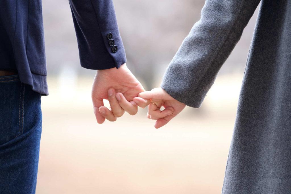 小指と小指を繋いで歩く男女