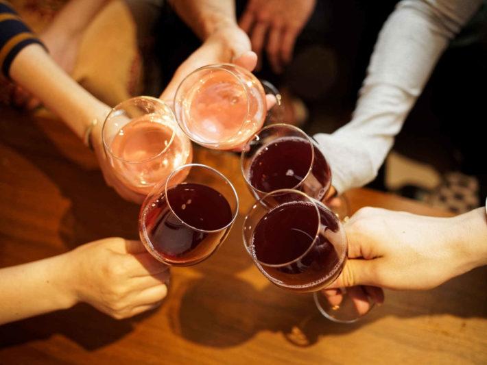 男女がグラスで乾杯し、パーティーしている画像