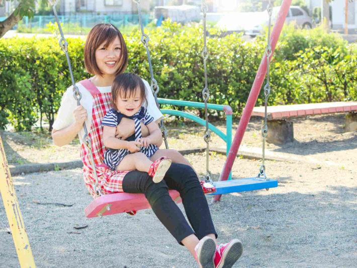 子供を膝に乗せてブランコしている保育士女性
