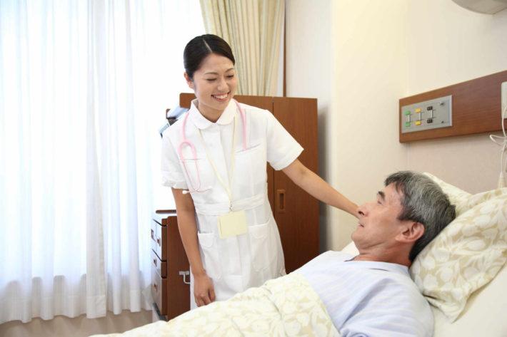 ベッドで寝ている男性を介抱する看護師