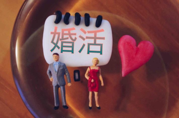 婚活と書かれたホワイトボードの前に置かれたミニチュアの男女
